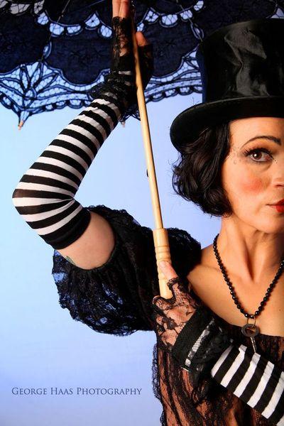 model with vintage black lace 80s dress, skeleton key necklace, top hat, black lace gloves, black and white striped gloves, black parasol